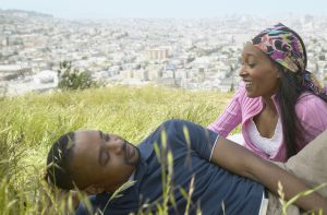 after fasting, pic of African couple sitting in grass on hill above city