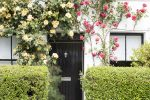 pic of Trailing red and yellow roses form a decorative arch over the door